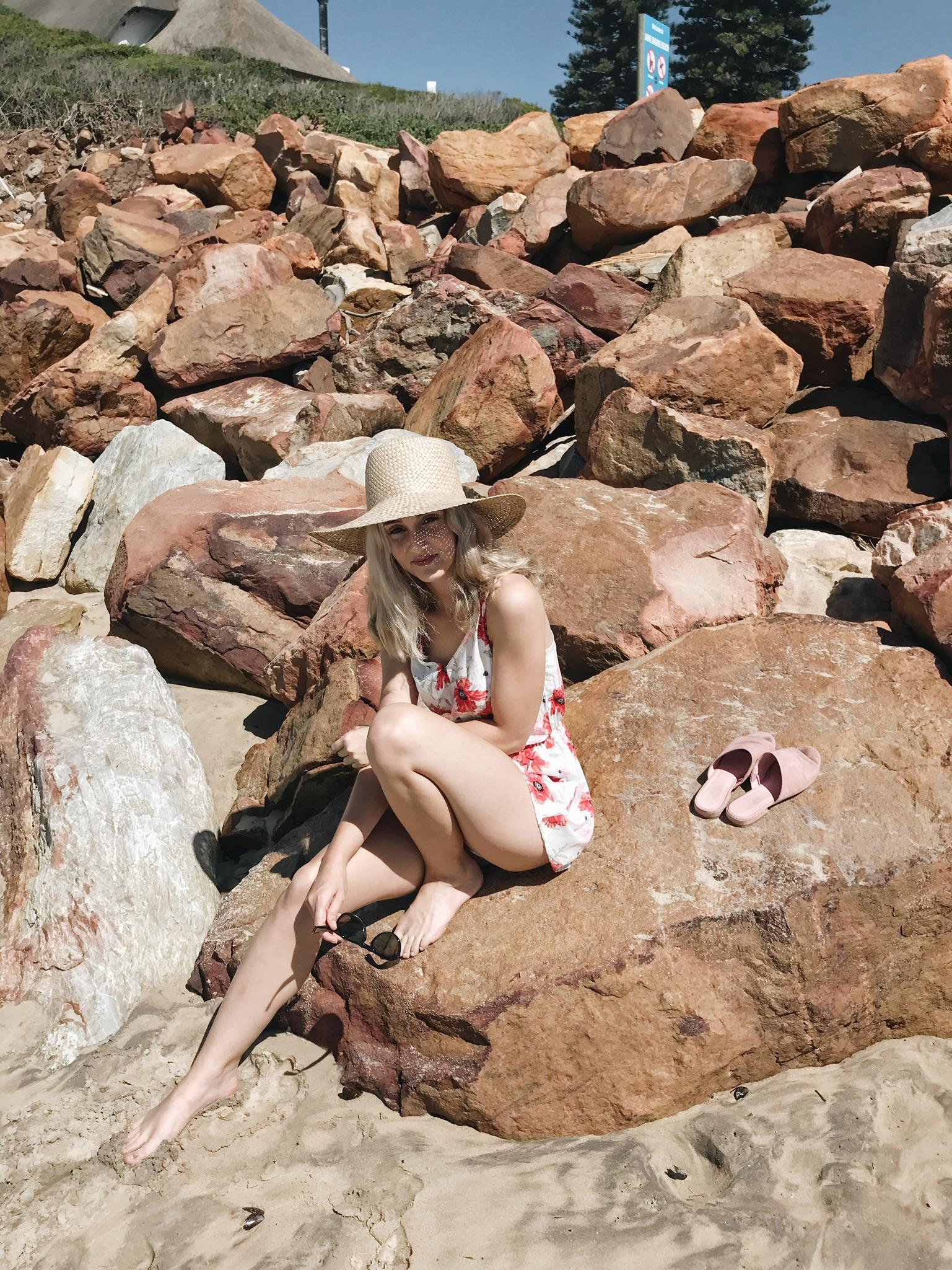 Lauren Carmen sits with her back arched, on the rocks