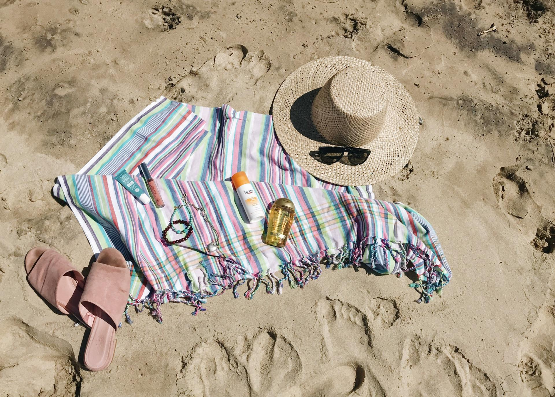Sarong, shoes, hat and sunglasses laid out on the beach